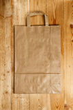 Paper bag on a wooden texture Royalty Free Stock Photo