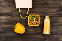 Paper-bag with yellow handles lying near box stewed vegetables Stock Image
