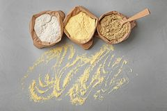 Paper bags with different types of flour. On gray background Stock Photography