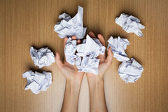 Paper ball in hand. With wooden table royalty free stock photo