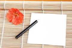 Paper on Bamboo Mat. A piece of paper with a pencil and flower arranged on a bamboo mat royalty free stock images