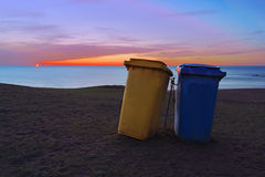 Paper bins on beach at sunset Stock Photo