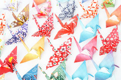 Paper birds. A group of origami cranes facing the same direction on a white background stock image