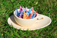 Paper birds. Colorful paper birds in a cup on the grass royalty free stock photography