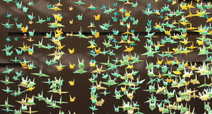 Paper birds. Yellow and green  paper birds hanging on strings from the ceiling Stock Images