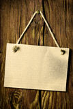 Paper board hanging on wooden wall. The paper board hanging on wooden wall royalty free stock photography