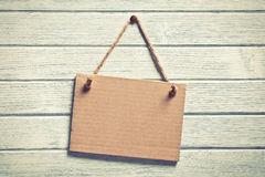Paper board hanging on wooden wall Royalty Free Stock Images