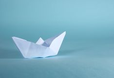 Paper boat. A paper boat on a blue soft background stock image