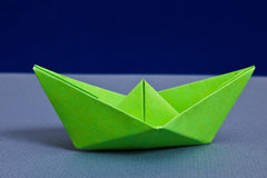 Paper boat. Green paper boat with blue background Royalty Free Stock Images