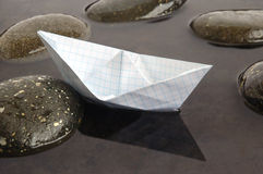 Paper boat. Floating in calm black water background stock photography