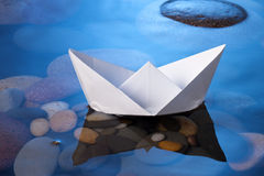 Paper Boat. A white paper boat floating on a blue water surface