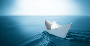 Paper boat. Origami paper sailboat sailing on blue water