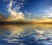 Paper Boat. And a beautiful Tropikal sunset royalty free stock photos