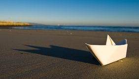 Paper boat. White paper boat on the beach stock image