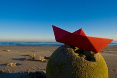 Paper boat. Red paper boat wrecked on an old ball stock photos