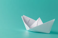 Paper boat on aquamarine background Stock Photos