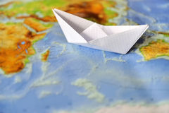 Paper boat on a background map of the world Royalty Free Stock Image