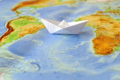Paper boat on a background map of the world Royalty Free Stock Photos