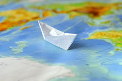 Paper boat on a background map of the world Stock Image