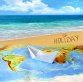 Paper boat on a background map of the world Stock Photography