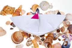 Paper boat on background from sea shells Royalty Free Stock Photography