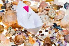 Paper boat on background from sea shells Stock Photography