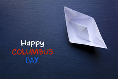 Paper boat on a blackboard and text Happy Columbus Day Stock Image