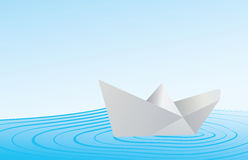 Paper boat on blue water Stock Photos