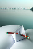 Paper boat on a book. Paper boat, pencil and an open book against a lake background Royalty Free Stock Photos