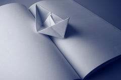 Paper boat on a book. Concept with a paper boat and an open plain book Stock Image