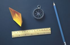 Paper boat and compass on desk stock photography