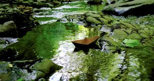 Paper boat floating in the fast flowing forest stream. 4k stock video footage