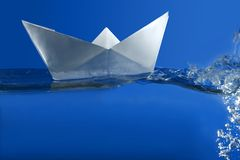 Paper boat floating over blue real water Stock Photos