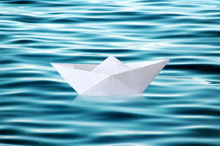 Paper boat floating on rippled water Stock Images