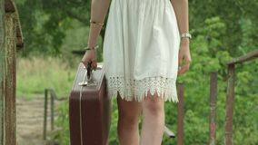 The girl in a white dress carries suitcase in hand brown. Slow motion. stock video
