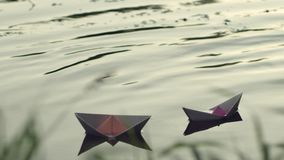 Two paper boats adrift in the river. stock video