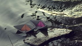 Two paper boats moored to the shore. stock footage