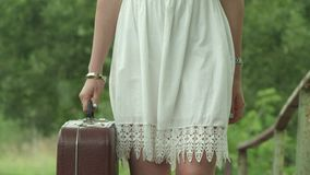 The girl in a white dress carries suitcase in hand brown. Slow motion. stock footage