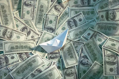 Paper boat floating on the sea of money Stock Images
