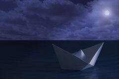 Paper boat floating in the sea at night Stock Image