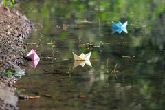 Paper boat floating on water Stock Images
