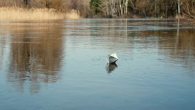 A paper boat is floating on the water. Origami boat floats away into the distance along the river stock footage