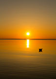 Paper boat floating in the water during sunset Stock Photo