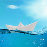 Paper boat floating among the waves in the ocean Stock Photos
