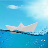 Paper boat floating among the waves in the ocean Royalty Free Stock Photography