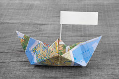 Paper boat folded out of a map with a time-out sign on an grey w Stock Images