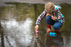 Paper boat. Girl runs the pink paper boat in a puddle in the rain, spring royalty free stock photo
