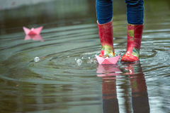 Paper boat. Girl runs the pink paper boat in a puddle in the rain, spring stock photos