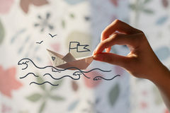Paper boat in hand. Painted sea with waves and seagulls Royalty Free Stock Images