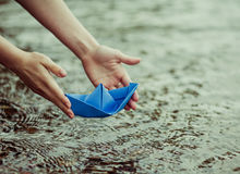 Paper boat. Hands of a young woman with a paper boat by the lake in summertime (focus on the beat stock photography